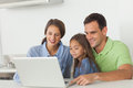 Family using a laptop on the kitchen table beautiful Royalty Free Stock Photo