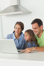 Family using a laptop pc on the kitchen table beautiful Royalty Free Stock Photography