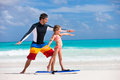 Family vacation father and daughter at beach practicing surfing position Stock Image