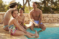 Family On Vacation Relaxing By Outdoor Pool Royalty Free Stock Photo