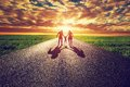 Family walk on long straight road, way towards sunset sun Royalty Free Stock Photo