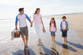 Family walking along beach with picnic basket towards camera Stock Photos