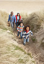 Family Walking Along Dunes On Winter Beach Stock Image