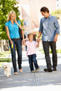 Family walking dog in city street Stock Photography
