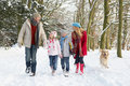 Family Walking Dog Through Snowy Woodland Royalty Free Stock Photos