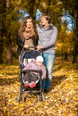 Family walking with pram at autumn park young Stock Image