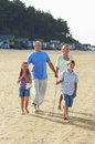 Family walking on sand at beach full length of a Stock Photos