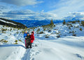 Family walking on winter mountain slope Royalty Free Stock Images