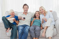 Family watching television sitting on sofa with pop corn Royalty Free Stock Photography