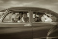 image photo : Family Waving Hello in Vintage Car