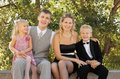Family wearing holiday clothes sit and smile Royalty Free Stock Photo