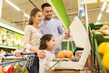 Family weighing oranges on scale at grocery store Royalty Free Stock Photo