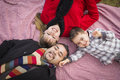 Family in winter clothing laying on their backs in park young mixed race picnic blanket the together Royalty Free Stock Image
