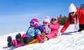 Family winter playing young mother with children riding with snow slides in time Stock Image