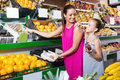 Family of woman and daughter buying various fruits Royalty Free Stock Photo