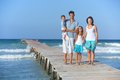 Family on wooden jetty of four by the ocean Royalty Free Stock Image