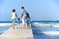 Family on wooden jetty of four by the ocean back view Royalty Free Stock Photos