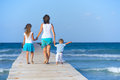 Family on wooden jetty mother with his two kids walking by the ocean back view Royalty Free Stock Image