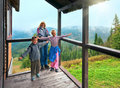 Family on wooden mountain cottage porch Stock Images