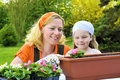 Young woman and little girl gardening in spring, planting flower seedlings, smiling mother and her happy child working in garden