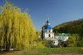 Famous churches of kiev orthodox church is sunlit in the middle spring park the blue sky a dark green slope and a large yellowish Stock Images
