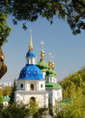 Famous churches of kiev orthodox church is sunlit in the middle spring park golden crosses are shining on blue and green domes Royalty Free Stock Photography