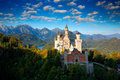 Famous fairy tale Castle in Bavaria, Neuschwanstein, Germany, morning with blue sky with white clouds Royalty Free Stock Photo