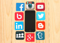 Famous social media icons around iPhone on wooden background