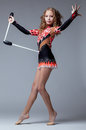 Fancy artistic gymnast dancing with mace in studio Stock Photo