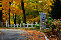 Fancy fall driveway pillars with lanterns a during the surrounded by beautiful colors maple trees hydrangeas and a white fence Royalty Free Stock Photography