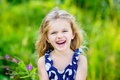 Fanny and beautiful laughing little girl with long blond hair curly outdoor portrait in summer park on bright sunny day child in Royalty Free Stock Photos