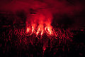 Fans burn red flares at rock concert. Cheering crowd at concert. Fire show. Royalty Free Stock Photo