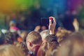 Fans photographing music band live performing on stage concert in open arena selective focus toned image with sunflares Royalty Free Stock Photo
