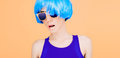 Fantastic fashion lady in blue wig and glasses on yellow background Stock Photography