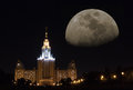 Fantastic moscow night moon cityscape view on the state university building with streets lights and huge arising on dark sky Royalty Free Stock Photography