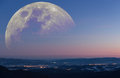Fantastic mountain landscape moon the winter early morning view from the mountains to a valley with towns emitting light with huge Royalty Free Stock Photography