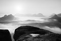 Fantastic sunrise on the top of the rocky mountain with view into misty valley. Black and white Royalty Free Stock Photo