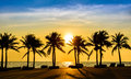Fantastic tropical beach with palms at sunset Royalty Free Stock Photo