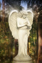 Fantastical glowing statue of an angel in magical garden setting Royalty Free Stock Image