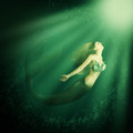 Fantasy beautiful woman mermaid with tail fish and long developing hair swimming in the sea under water Stock Photography