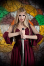 Fantasy style portrait of a woman in medieval dress with the sword looking at camera Royalty Free Stock Photo