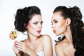 Fantasy woman teasing another with lollipop couple of women sweets posing Stock Photography