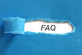 Faq appearing behind blue color paper Stock Images