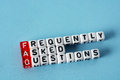 Faq frequently asked questions written on cubes on blue background Stock Photo