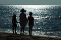Farewell to the sea the end of vacation women and kids silhouettes against glittering water surface Stock Photos