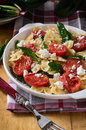 Farfalle pasta butterfly shaped pasta with tomatoes spinach and cheese in a plate on a wooden table Stock Image