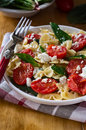 Farfalle pasta butterfly shaped pasta with tomatoes spinach and cheese in a plate on a wooden table Royalty Free Stock Image