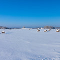Farm with a barn and horses in winter bales of hay laying the snow on field Stock Photography