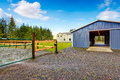 Farm blue barn shed and gravel driveway. Royalty Free Stock Photo