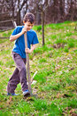 Farm boy digging with a shovel Stock Photography